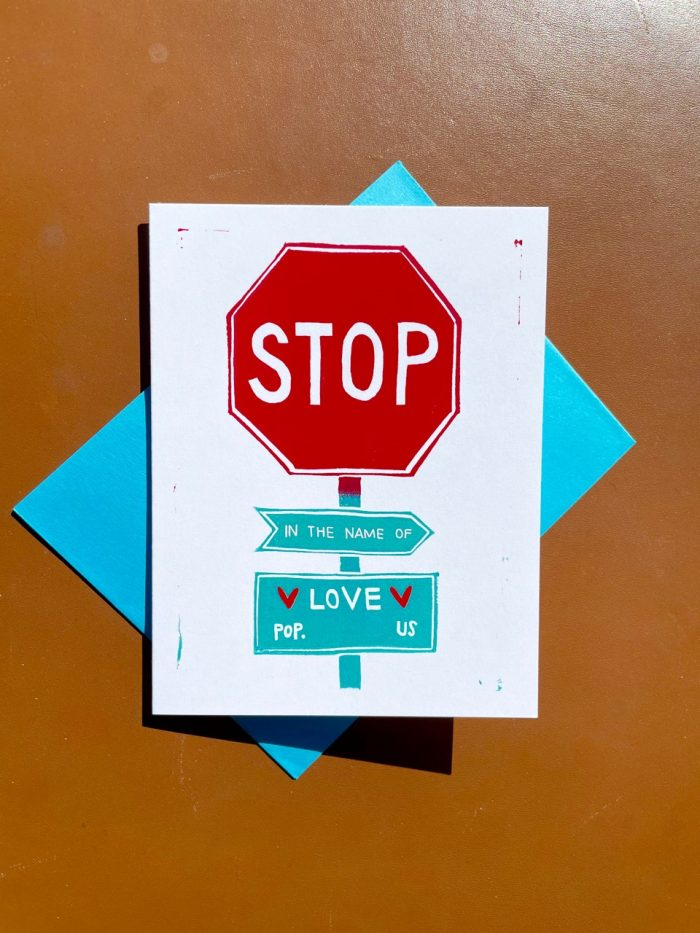"""White folding card with red stop sign and turquoise signs below reading """"in the name of love"""" and """"population us"""""""