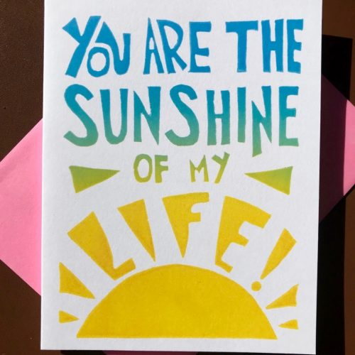 "Hand-carved lettering in blue, green, and yellow ombre on a white folding card that reads ""You are the sunshine of my life"""