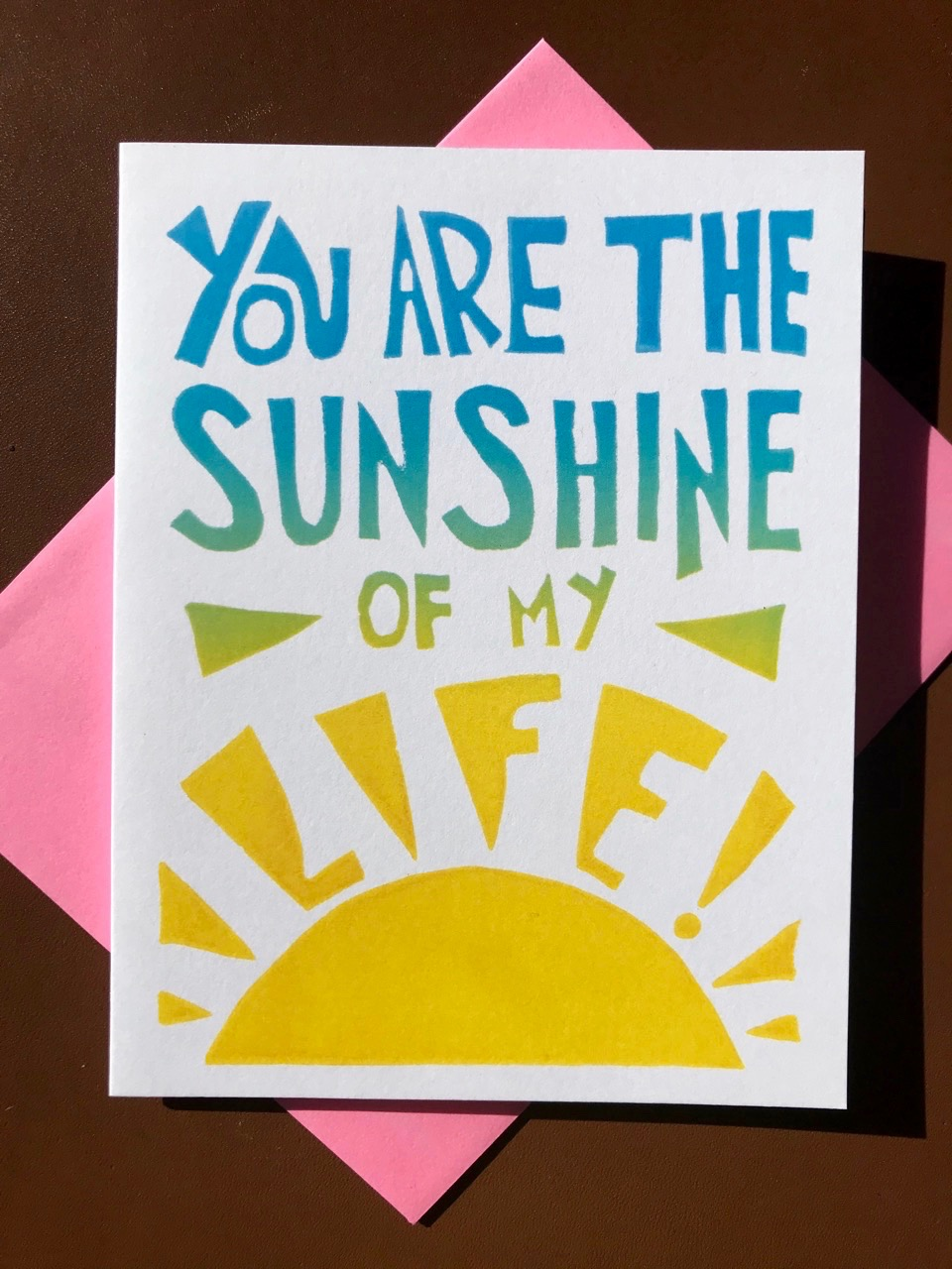 """Hand-carved lettering in blue, green, and yellow ombre on a white folding card that reads """"You are the sunshine of my life"""""""