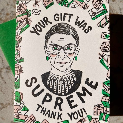 "Hand-drawn bust illustration of Ruth Bader Ginsburg in her iconic lace collar with handlettered text that reads ""Your gift was supreme, thank you!"", letterpress printed in green, light pink, and black on a white textured folding card"