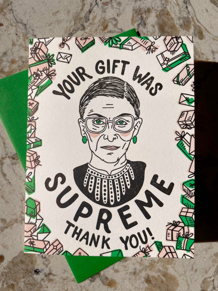 """Hand-drawn bust illustration of Ruth Bader Ginsburg in her iconic lace collar with handlettered text that reads """"Your gift was supreme, thank you!"""", letterpress printed in green, light pink, and black on a white textured folding card"""