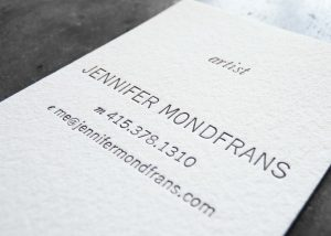 Close up of a letterpress printed business card on premium textured paper; very simple card with clean, modern sans serif type printed in black. Vertical orientation.