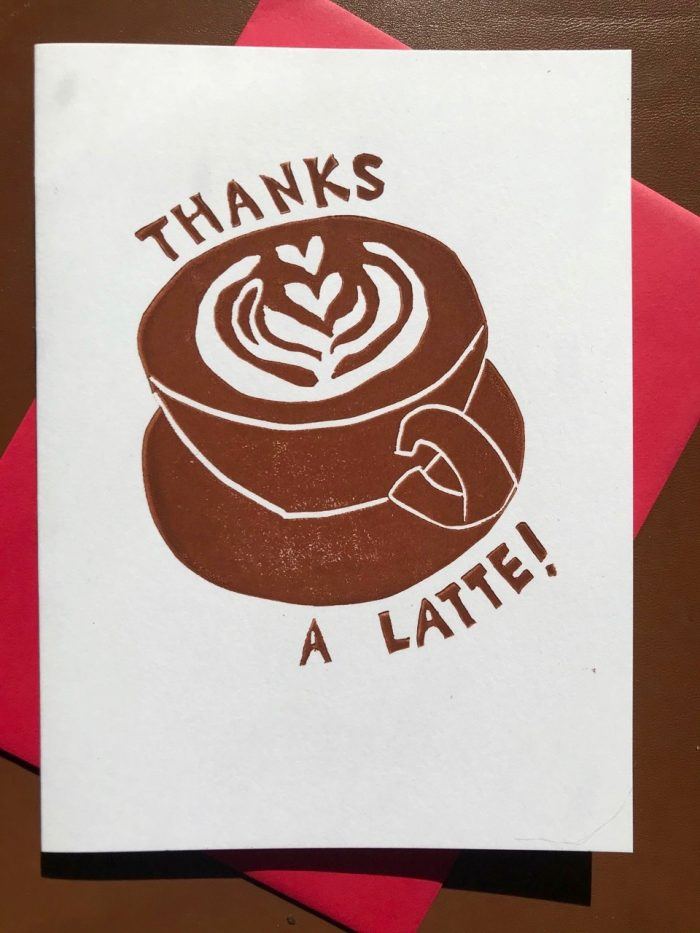 "Brown illustration of a latte in a short handled mug and saucer with the foam shaped into hearts along with hand-lettering that reads ""thanks a latte""."
