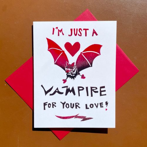 "White folding card with red and black gradient across hand-lettering and a bat with a heart above its head. Hand-lettering reads ""I'm just a vampire for your love!"""