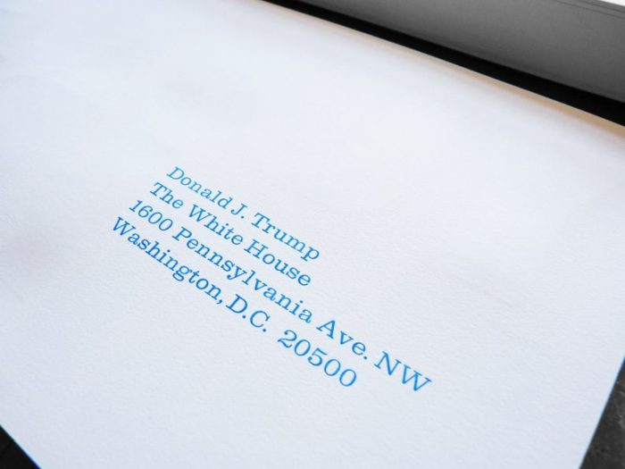 "White postcards letterpress printed in blue ink with ""You're Fired!!"" on one side and the president's address on the other side"