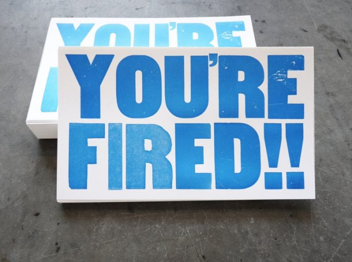 "White postcard letterpress printed with ""You're Fired!!"" in blue ink on white card stock"