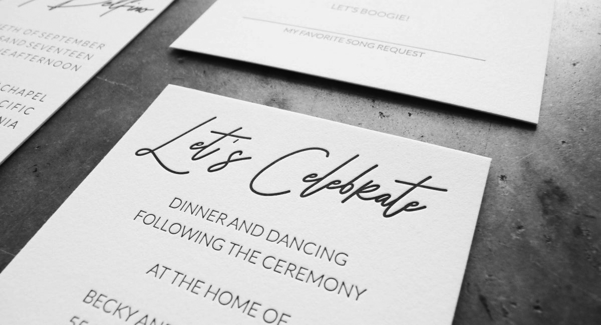 "A black and white letterpress printed card reading ""Let's Celebrate"" in a hand lettered / handwritten font, paired with a clean, modern sans serif font. Part of a wedding invitation suite"