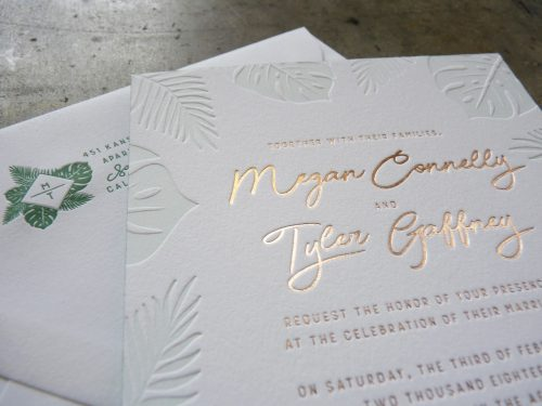 Close up image of a letterpress printed and foilstamped wedding invitation featuring palm and monstera leaves printed in a light green tonal letterpress, and modern script combined with modern sans serif type printed in gold foil. Behind the invitation is an envelope with rich green letterpress, featuring a custom monogram and the return address.