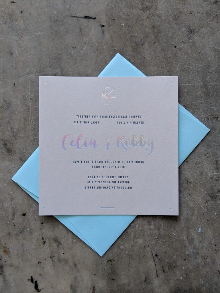 """Square grey wedding invitation with holographic foil creating a shiny rainbow effect and black letterpress. Lines and dots form a minimalist """"border,"""" and the invitation has a custom monogram of the couple's initials at the top. A blue envelope is placed behind the wedding invitation."""